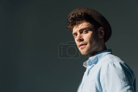 Photo for Handsome serious man in brown hat standing in sunlight - Royalty Free Image
