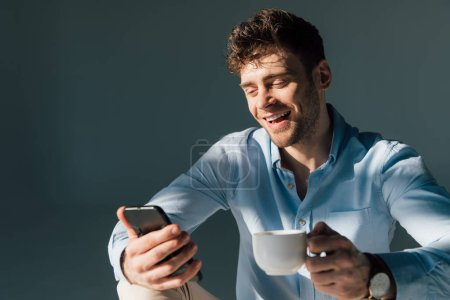 Photo for Cheerful man using smartphone and holding coffee cup - Royalty Free Image
