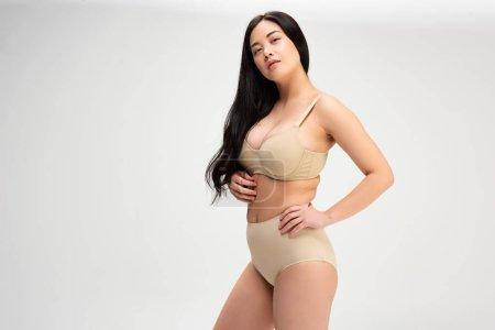 Foto de Bastante joven mujer morena en ropa interior mirando a cámara aislada en gris, concepto de positividad de cuerpo - Imagen libre de derechos