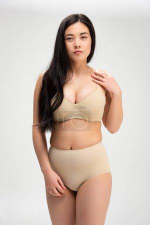 Foto de Mujer bastante sobrepeso en ropa interior mirando a cámara aislada en gris, concepto de positividad de cuerpo - Imagen libre de derechos