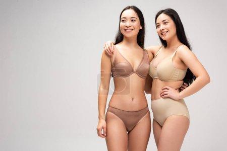 Foto de Dos mujeres bastante multiétnicas en lencería abrazándose y sonriendo aislado en gris, concepto de positividad de cuerpo - Imagen libre de derechos