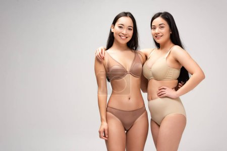 Foto de Dos mujeres multiétnicas atractivas en ropa interior abrazando y mirando a cámara aislada en gris, concepto de positividad de cuerpo - Imagen libre de derechos