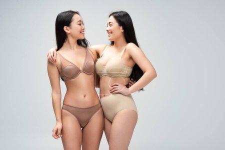 Foto de Dos mujeres multiétnicas alegres en ropa interior abrazando y mirando mutuamente aislados en gris, concepto de positividad de cuerpo - Imagen libre de derechos