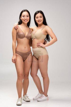 Foto de Dos mujeres multiculturales alegres en ropa interior abrazando y mirando a cámara, concepto de positividad de cuerpo - Imagen libre de derechos