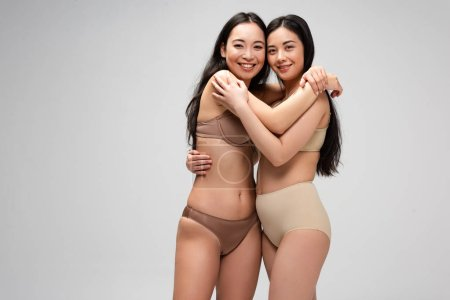 Photo for Two happy young multicultural women embracing and looking at camera isolated on grey, body positivity concept - Royalty Free Image