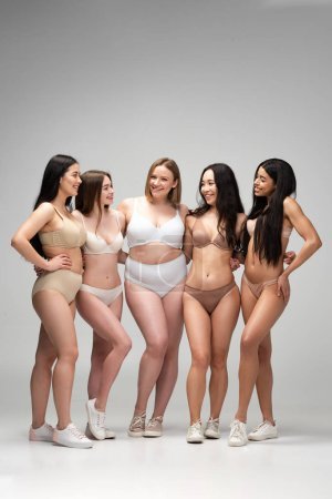 Photo pour Five cheerful young multiethnic women in lingerie standing together and looking at each other, body positivity concept - image libre de droit