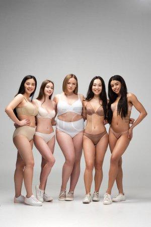 Foto de Cinco bonitas a jóvenes multiétnicas en ropa interior posando en la cámara, el concepto de positividad de cuerpo - Imagen libre de derechos