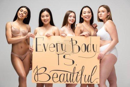"""Photo pour Cinq jeunes femmes multiculturelles souriantes tenant une pancarte avec le lettrage """"chaque corps est beau"""" isolé sur gris - image libre de droit"""