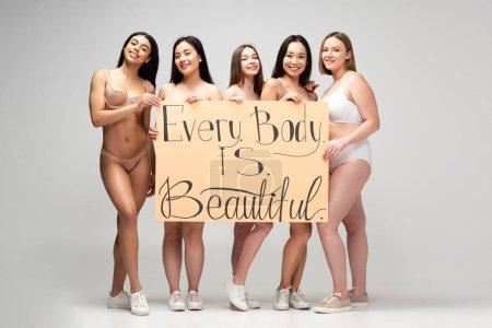 """Photo pour Cinq jolies filles multiculturelles tenant une pancarte avec l'inscription """"chaque corps est beau"""" - image libre de droit"""