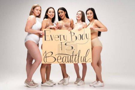 """Foto de Cinco chicas multiétnicas alegres celebración de cartel con la inscripción """"cada cuerpo es hermoso"""" - Imagen libre de derechos"""