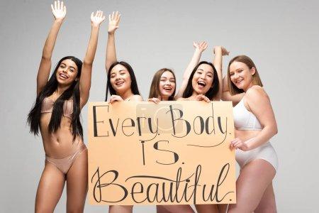 """Foto de Cinco niñas multiétnicas felices sosteniendo pancarta con letras """"cada cuerpo es hermoso"""" y agitando las manos aisladas en gris - Imagen libre de derechos"""