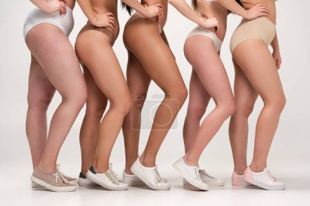 Photo for Partial view of five multiethnic women in underwear and sneakers posing with hands on hips, body positivity concept - Royalty Free Image