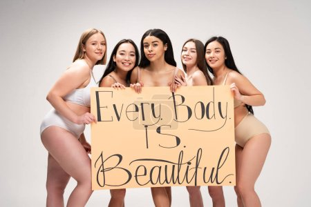 "Photo for Five smiling multiethnic girls holding placard with ""every body is beautiful"" lettering isolated on grey - Royalty Free Image"