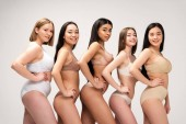 five smiling multiethnic women in lingerie posing with hands on hips isolated on grey, body positivity concept