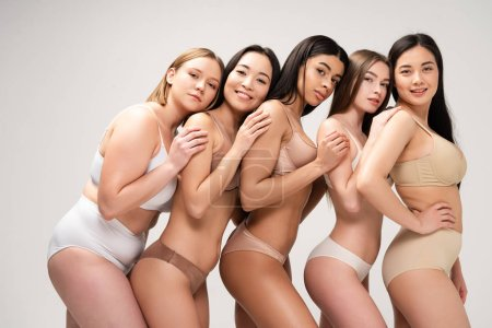 Photo pour Five pretty multiethnic girls in lingerie leaning on each other and looking at camera isolated on grey, body positivity concept - image libre de droit