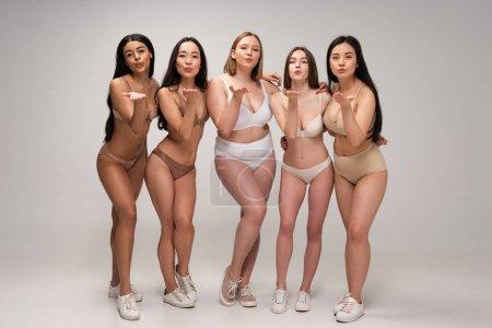 Foto de Cuerpo de cinco chicas multiculturales atractivas en ropa interior enviando besos de aire, concepto de positividad - Imagen libre de derechos