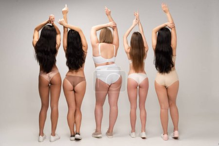 Foto de Vista posterior de cinco mujeres multiculturales en ropa interior con las manos levantadas, concepto de positividad de cuerpo - Imagen libre de derechos