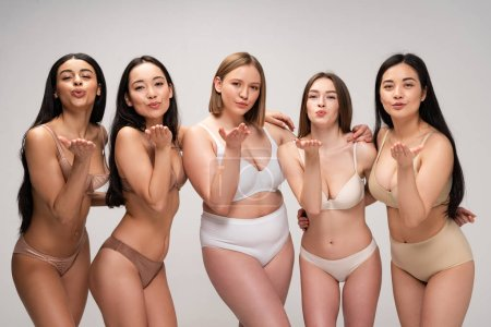Foto de Cinco niñas bastante multiculturales en ropa interior enviando aire besos aislados en gris, concepto de positividad de cuerpo - Imagen libre de derechos