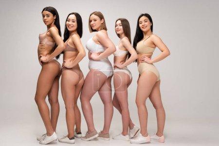 Foto de Cinco jóvenes mujeres multiétnicas en ropa interior posando con las manos en las caderas, del cuerpo concepto de positividad - Imagen libre de derechos