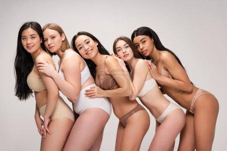 Photo pour Cinq jeunes femmes multiethniques heureuses en sous-vêtements s'appuyant l'une sur l'autre isolées sur le concept gris de positivité corporelle - image libre de droit
