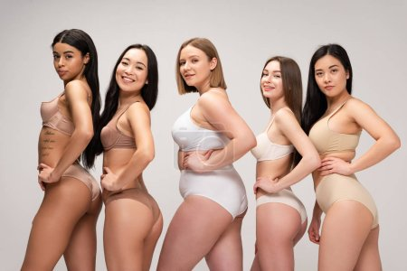 Photo pour Five pretty multiethnic girls in lingerie posing at camera with hands on hips isolated on grey, body positivity concept - image libre de droit