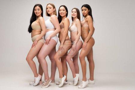 Foto de Cinco hermosa mujer multiétnica en ropa interior y zapatillas posando a la cámara y sonriendo, concepto de positividad de cuerpo - Imagen libre de derechos