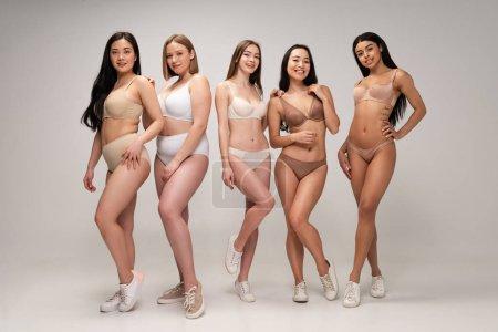 Foto de Cinco mujeres multiculturales alegres en ropa interior y zapatillas posando en la cámara, del cuerpo concepto de positividad - Imagen libre de derechos