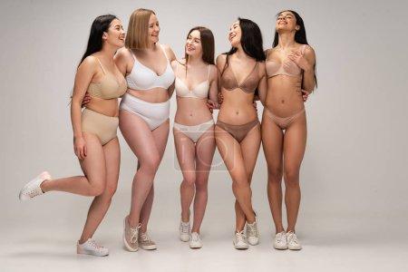 Foto de Cinco mujeres jóvenes multiculturales alegres en ropa interior abrazando mientras posando en la cámara, del cuerpo concepto de positividad - Imagen libre de derechos