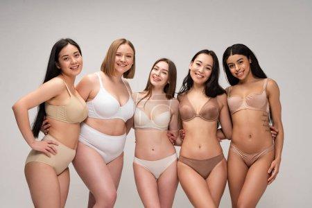 Foto de Cinco mujeres multiculturales atractivas en ropa interior abrazando mientras posando en cámara aislaron en concepto de positividad de cuerpo gris, - Imagen libre de derechos
