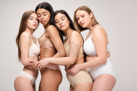 Photo for Five dreamy multiethnic girls in underwear hugging and leaning on each other isolated on grey, body positivity concept - Royalty Free Image