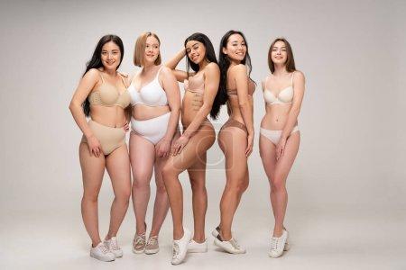Foto de Cinco niñas multiétnicas sonriendo sonriendo y posando a la cámara, del cuerpo concepto de positividad - Imagen libre de derechos