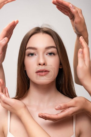 Photo for Portrait of beautiful young woman surrounded by female hands isolated on grey - Royalty Free Image