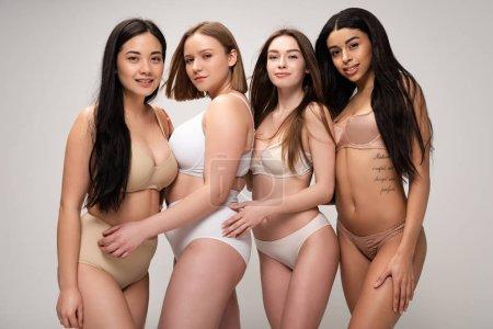Photo pour Quatre belles filles multiculturelles souriant et regardant la caméra isolée sur gris, concept de positivité du corps - image libre de droit