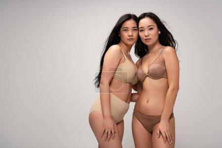 Foto de Aislaron dos belleza multiétnica las mujeres jóvenes en ropa interior mirando a cámara en concepto de positividad de cuerpo gris, - Imagen libre de derechos