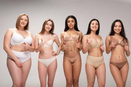 Foto de Cinco niñas bastante multiculturales en ropa interior mostrando los pulgares aislado en concepto de positividad de cuerpo gris, - Imagen libre de derechos