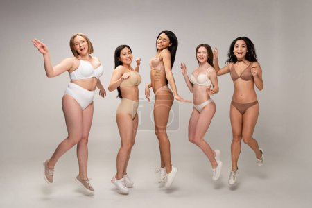 Photo for Five pretty multicultural girls in lingerie having fun and jumping, body positivity concept - Royalty Free Image
