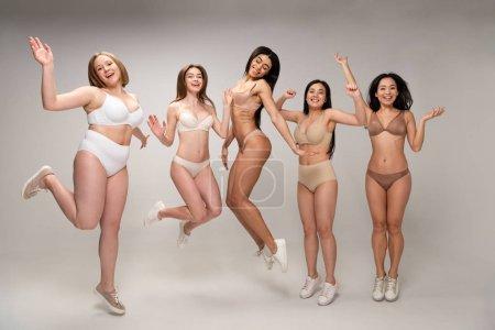 Foto de Concepto de positividad del cuerpo cinco atractivo multicultural las mujeres jóvenes en ropa interior te diviertes y saltando, - Imagen libre de derechos