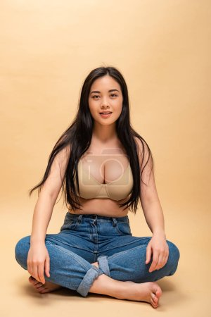 Photo for Pretty girl in blue jeans and bra sitting with crossed legs, body positivity concept - Royalty Free Image