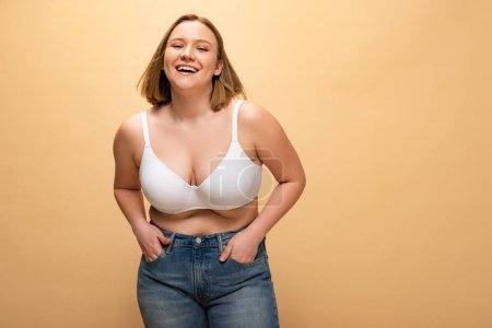 Photo for Happy overweight girl holding hands in pockets while posing at camera isolated on beige, body positivity concept - Royalty Free Image