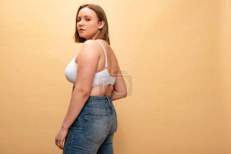 Foto de Chica bastante sobrepeso en vaqueros y sujetador mirando a cámara aislada en color beige, concepto de positividad de cuerpo - Imagen libre de derechos