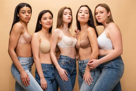 Photo pour Five confident multicultural girls in blue jeans and bras posing at camera isolated on beige, body positivity concept - image libre de droit