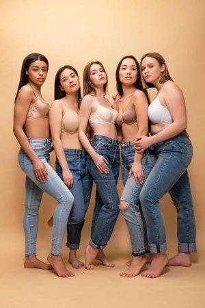 Foto de Cuerpo de cinco chicas multiculturales serias en jeans azul y bras mirando a cámara, junto, concepto de positividad - Imagen libre de derechos