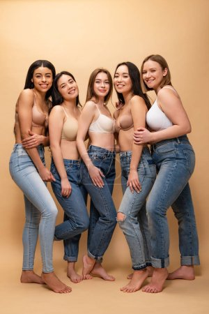 five cheerful multicultural women in blue jeans and bras smiling and looking at camera, body positivity concept
