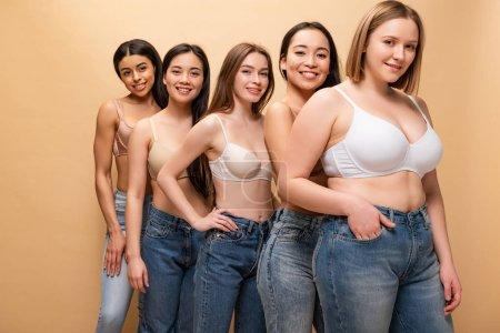 cinco chicas muy multiculturales en vaqueros azules y sujetadores sonriendo y mirando a la cámara aislada en beige, concepto de positividad corporal