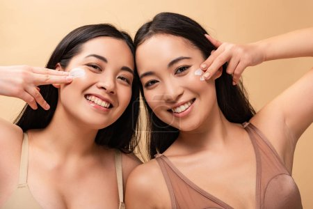Photo for Two happy multicultural women applying cosmetic cream on face and looking at camera isolated on beige - Royalty Free Image