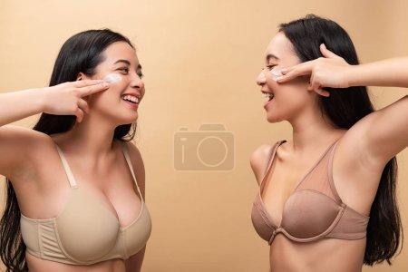 Photo pour Deux filles multiculturelles heureuses appliquant de la crème cosmétique sur le visage et se regardant isolées sur beige - image libre de droit