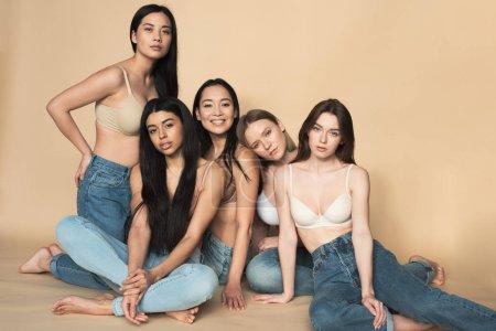 Foto de Cinco hermosas mujeres jóvenes multiculturales en jeans azul y bras sentado y mirando a cámara - Imagen libre de derechos