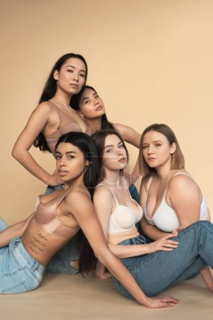 Photo for Five multicultural women in blue jeans and bras looking at camera, body positivity concept - Royalty Free Image