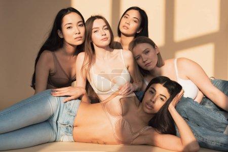 Foto de Cinco chicas bastante multiculturales posan a cámara en luz del sol, del cuerpo concepto de positividad - Imagen libre de derechos