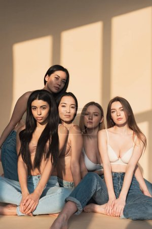 Photo for Five pensive multicultural girls sitting in sunlight and looking at camera - Royalty Free Image
